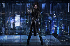 Future woman dressed in black latex with a huge gun in a buildin Stock Photos