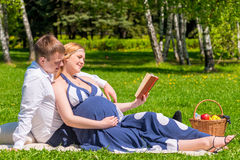 Future young parents reading the book on picnic. For children Royalty Free Stock Images