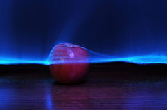 Futuristic Apple Background. Red apple with colorful abstract lasers going through and above the fruit. Background copyspace above Stock Photos