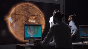 Futuristic astronomy team and solar presentation. A futuristic astronomy team discuss emergency response tactics during a presentation on a large screen stock footage