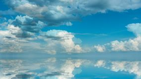 Futuristic background consisting of Time lapse clip of white fluffy clouds over blue sky and their reflection, video