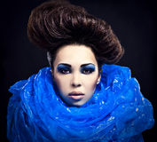 Futuristic beautiful young female face with blue fashion make-up. Royalty Free Stock Photo
