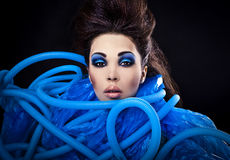 Futuristic beautiful young female face with blue fashion make-up. Stock Images
