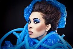 Futuristic beautiful young female face with blue fashion make-up. Stock Image