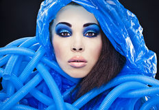 Futuristic beautiful young female face with blue fashion make-up. Royalty Free Stock Images