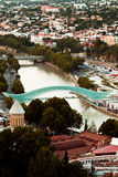Futuristic Bridge of Peace and old buildings in Tbilisi, Georgia. Aerial view of futuristic glass and iron bow-shaped pedestrian Bridge of Peace and old building Stock Images