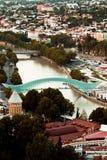 Futuristic Bridge of Peace and old buildings in Tbilisi, Georgia Stock Images