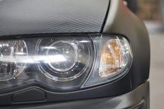 Futuristic car headlight. Carbon hood Stock Photos