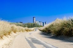 Futuristic city looming at the and of an empty road, which runs through dunes. Summer. Vacation. Path to unknown.Path to success. royalty free stock photos