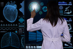 A futuristic computer interface floats in front of a female doctor. Royalty Free Stock Image