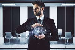 Futuristic concept. Handsome young businessman holding abstrat digital projection in modern meeting room interior. Futuristic concept. 3D Rendering Royalty Free Stock Image