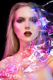 Futuristic conceptual portrait of a beautiful girl covered by wrinkled transparent plastic colored by blue and red lights royalty free stock photo
