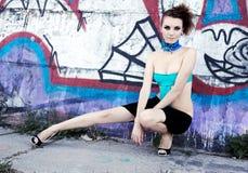 Futuristic fashion model. Outdoors sitting near graffiti wall Royalty Free Stock Images