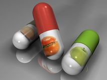 Futuristic food. Pills on a grey background with pictures of food on it Stock Photography