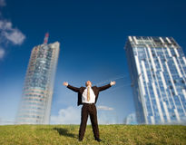 Futuristic freedom. Happy business man standing on green grass - arms outstretched Royalty Free Stock Images