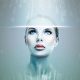 Futuristic girl. Abstract futuristic woman looking at data flow in a virtual display Royalty Free Stock Photo