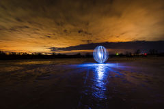 Futuristic glowing sphere on the surface of frozen lake at the background of night landscape Stock Photography