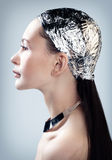 Futuristic image. Portrait of a young woman wearing a hat from the foil Royalty Free Stock Images