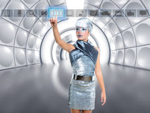 Futuristic kid girl silver touching finger icons. Futuristic kid girl in silver touching finger icons on glass transparent holographic screen royalty free stock photo