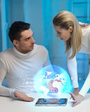 Futuristic man and woman with globe hologram Stock Image