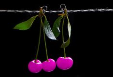 Futuristic neon pink cherry on a string with clips. On a contrasting black background stock image