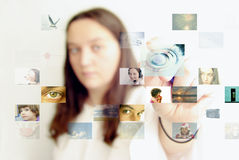 Futuristic photo selection. Young girl selecting photographs. Futuristic photo selection and sharing, social networking concept Royalty Free Stock Image