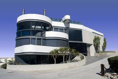 Futuristic round white house. Contemporary white home made with stucco and glass Stock Image