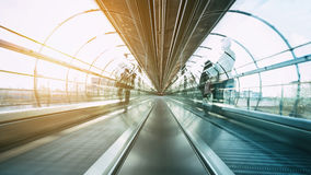 Futuristic skywalk with blurred passengers Stock Photo