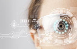 Futuristic smart glasses. Young woman loking at virtual graphics in futuristic background Stock Photos