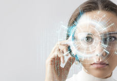 Futuristic smart glasses. Young woman loking at virtual graphics in futuristic background Royalty Free Stock Images