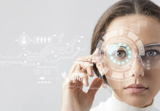 Futuristic smart glasses. Young woman loking at virtual graphics in futuristic background Stock Image
