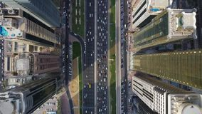 Futuristic top aerial drone shot of long busy highway road and modern skyscrapers in Dubai big city panorama