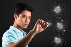 Futuristic touchscreen interface. Vietnamese young man shifting hexagon figure on futuristic touchscreen interface Stock Image