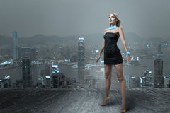 Futuristic woman in night city. Futuristic fashion woman posing in small black dress at cityscape of night hongkong city Royalty Free Stock Images