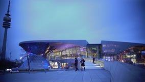 Futuristische architectuur, mensen die dichtbij verlicht modern winkelcomplex lopen stock footage