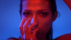 Futuristische mannequin in rode en blauwe neonlichten die gezicht behandelen met handen vreemd en vast in camera kijken stock video