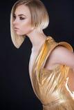 Futuristische sexy Frau im goldenen Kleid Stockfotos