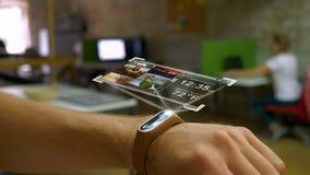 Futuristisk apparat på en mans hand, ett hologram, smart klockakontor i bakgrunden stock video