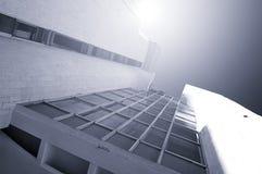 Futuristisk bakgrund för arkitektur - nedersta sikt för perspektiv av hög byggnad av betong och exponeringsglas arkivbilder