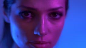 Futuristisk modemodell i färgrika vänd för neonljus till kameran och klockor allvarligt och fast in i den i studio stock video