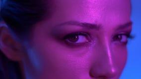 Futuristisk modemodell i profil i färgrika purpurfärgade och blåa neonljus som fast beslutsamt håller ögonen på in i kamera arkivfilmer