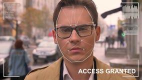 Futuristiskt och teknologiskt avläsa av framsidan av en härlig man för ansikts- erkännande och den avlästa personen