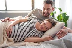 Futurs parents heureux proliférant dans la literie ensemble image stock