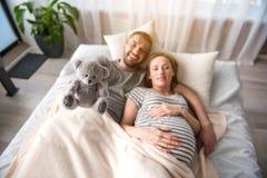 Futurs parents insouciants jouant avec le jouet mou dans la chambre à coucher photographie stock libre de droits