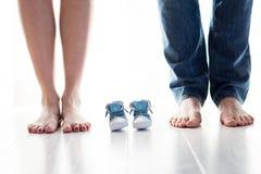 Futurs pieds de maman et de papa avec de petites chaussures de bébé Photo libre de droits