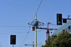Futurystyczna kula ziemska z budowa żurawiami w tle otaczającym czerwieni i zieleni światłami ruchu zdjęcie royalty free