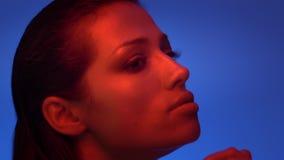 Futurystyczny moda model w czerwonych, błękitnych neonowych światłach dotyka jej wargi tenderly jest i zdjęcie wideo