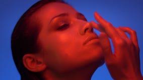 Futurystyczny moda model w czerwonych i błękitnych neonowych światłach dotyka jej twarz wzdłuż konturu jest poważny zdjęcie wideo