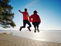 Fuuny happy lovers jump together. Woman and man hand in hand royalty free stock images