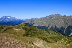 Fußweg in den Alpenwiesen und in felsigen Bergen bedeckt mit Schnee Stockfotos